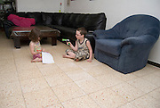 2 children boy aged 5 and girl aged 3 playing on the floor in their house Model Release Avalable