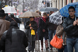 © Licensed to London News Pictures . 04/01/2014 . London , UK . Shoppers and tourists brave the wind and rain on London's Oxford Street today (Saturday 4th January 2013) as the January Sales continue . Photo credit : Joel Goodman/LNP