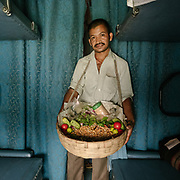 Peddler selling Raw peas. Throughout the journey, peddlers pop into the train compartments with all sorts of offerings,  to be bargained for a few rupees.<br /> Inside the Dibrugarh-Kanyakumari Vivek Express, the longest train route in the Indian Subcontinent. It joins Kanyakumari, Tamil Nadu, which is the southernmost tip of mainland India to Dibrugarh in Assam province, near the border with Burma.