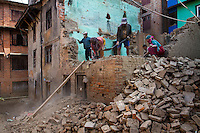Workers continue the demolition of a damaged home in Patan. Over a year after the earthquake, many structures remain unsound and must be strengthened or taken down. The Nepali government's failure to release funds donated by the international community has prevented timely assessment and action.