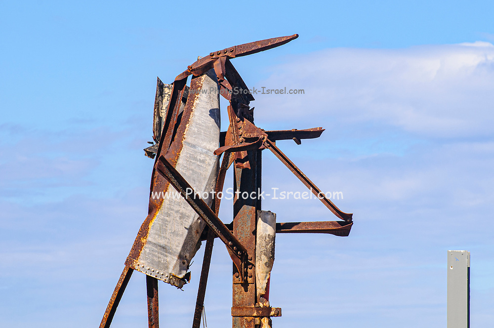 Old, rusted and decaying metal pylon from a demolished warehouse building with blue sky background