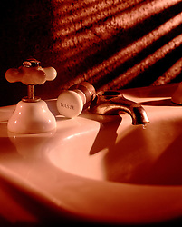 Old fashion sink leaks leaking water waste wasteful warm light shadows on textured wall small drop droplet of water from old fashion ceramic faucet CONCEPT STOCK PHOTOS