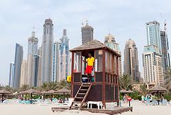 Lifeguard on duty at Jumeirah Beach with high rise apartment buildings at Dubai Marina to rear in Dubai United Arab Emirates , UAE