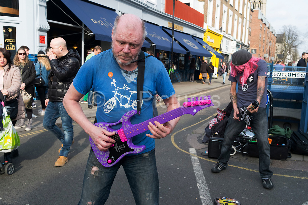 Two men on Portobello Road perform their busking performance to heavy rock music while pretending to play plastic toy guitars in London, England, United Kingdom. One has a Guitar Hero one, while the other a pink Hannah Montana guitar.