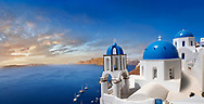 Panoramic sunset over the traditional Greek Orthodox churches of Oia (ia), Cyclades Island of  Thira, Santorini, Greece.<br /> <br /> The settlement of Oia had been mentioned in various travel reports before the beginning of Venetian rule, when Marco Sanudo founded the Duchy of Naxos in 1207 and feudal rule was instituted on Santorini. n 1537, Hayreddin Barbarossa conquered the Aegean islands and placed them under Sultan Selim II. However, Santorini remained under the Crispo family until 1566, passing then to Joseph Nasi and after his death in 1579 to the Ottoman Empire. .<br /> <br /> If you prefer to buy from our ALAMY PHOTO LIBRARY  Collection visit : https://www.alamy.com/portfolio/paul-williams-funkystock/santorini-greece.html<br /> <br /> Visit our PHOTO COLLECTIONS OF GREECE for more photos to download or buy as wall art prints https://funkystock.photoshelter.com/gallery-collection/Pictures-Images-of-Greece-Photos-of-Greek-Historic-Landmark-Sites/C0000w6e8OkknEb8