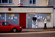 Man on phone in front of empty shop, 16th October 2006, Walthamstow, London, United Kingdom. A misplaced police sign stands against the wall with the words, dont accept lifts from strangers.