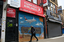 © Licensed to London News Pictures. 22/02/2021. London, UK. A man walks past Turkish Airline shop in Haringey, north London, on the day Prime Minister will announce the government's plans for relaxing Covid-19 restrictions in England. Boris Johnson will address the House of Commons at 3.30pm followed by a Downing Street news conference at 7pm. It is expected that shops, restaurants, hairdressers and pubs will reopen mid April. Photo credit: Dinendra Haria/LNP