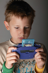 Portrait of a young boy playing with his Gameboy,