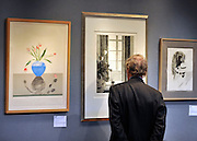 © Licensed to London News Pictures. 17/02/2012, London, UK. A man looks at prints before the auction. An auction of items by British artist David Hockney takes place at Christie's in London's South Kensington today, 17th February 2012. It features over 100 works by Hockney, including etchings, lithographs, drawings and photography. They are expected to sell for over £1m. The sale spans over 40 years of Hockney's career. Photo credit : Stephen Simpson/LNP