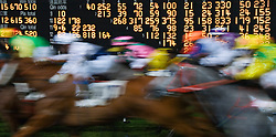 Blurred motion image of horses galloping past display board at Happy Valley racecourse in Hong Kong