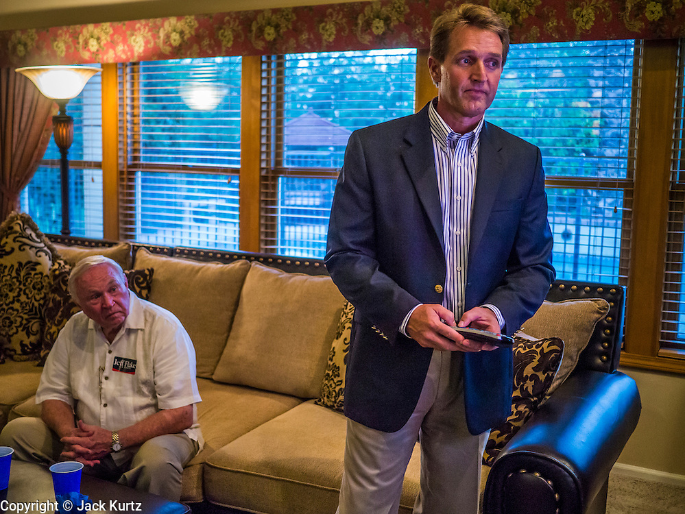 28 AUGUST 2012 - MESA, AZ:  Congressman JEFF FLAKE, (R-AZ) adjusts his TV in his home in Mesa, AZ, on election night. Flake is the incumbent Congressman from Arizona's 6th Congressional District. He won the Republican primary for the US Senate seat being vacated by retiring Senator Jon Kyl. Flake faced Arizona businessman and political newcomers Wil Cardon in the primary and won handily.    PHOTO BY JACK KURTZ