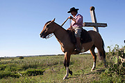 Brazilian male Gaucho cowboy riding a horse through a field pasture, cross in background. Working Gaucho Fazenda farm in Rio Grande do Sul, Brazil.