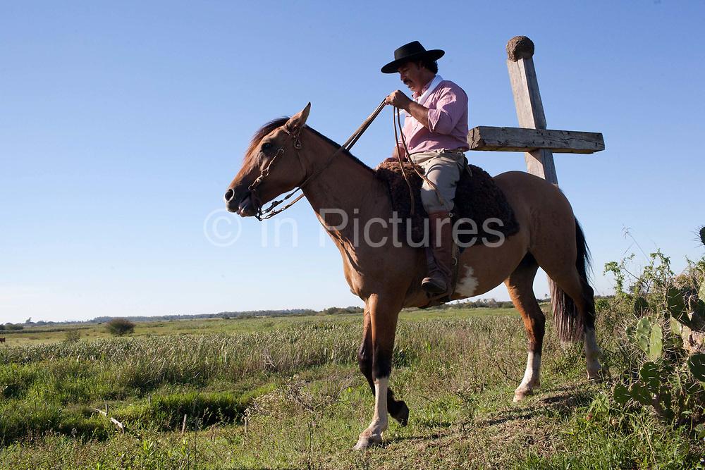 Brazilian male Gaucho cowboy riding a horse through a field pasture, cross in background. Working Gaucho Fazenda farm in Rio Grande do Sul, Brazil.