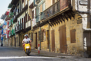 Motorcyclist on cobbled street passing medieval half-timbered architecture in Hondarribia, in Basque Country, Spain