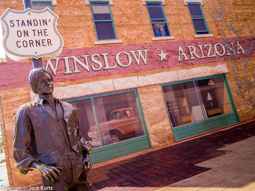 """15 JULY 2012 - WINSLOW, AZ: The Standin' on the Corner park at the intersection of Kinsley Avenue and Second Street in Winslow, AZ. The park is based on the Eagles song, written by Jackson Browne and Glenn Frey, the second verse is """"Well, I'm a standing on a corner, In Winslow, Arizona, And such a fine sight to see. It's a girl, my lord .In a flatbed Ford, Slowin' down to take a look at me"""" The park has a statue of Jackson Browne and flatbed Ford parked nearby. There is also a mural of the scene on a wall behind the statue.       PHOTO BY JACK KURTZ"""