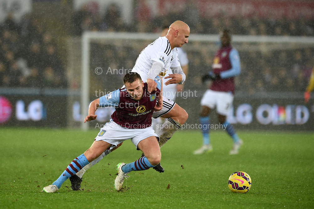 Jonjo Shelvey of Swansea city holds off Tom Cleverley of Aston Villa.Barclays Premier league match, Swansea city v Aston Villa at the Liberty stadium in Swansea, South Wales on Boxing Day, Friday 26th December 2014<br /> pic by Andrew Orchard, Andrew Orchard sports photography.