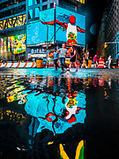 Times Square reflects in the street's puddles in Midtown Manhattan of New York City.