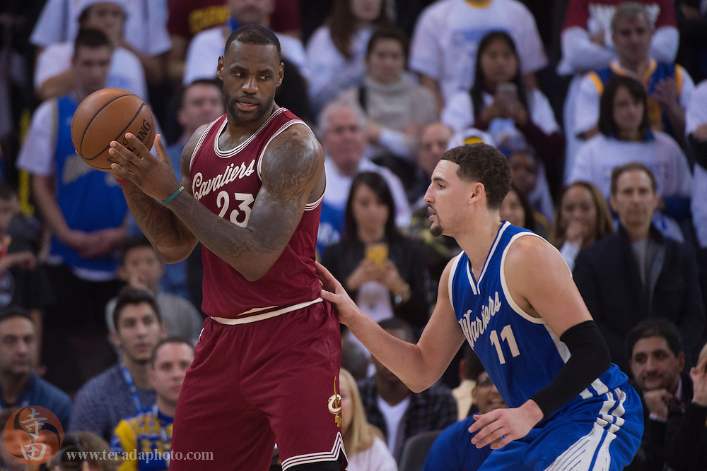 December 25, 2015; Oakland, CA, USA; Cleveland Cavaliers forward LeBron James (23) controls the basketball against Golden State Warriors guard Klay Thompson (11) during the fourth quarter in a NBA basketball game on Christmas at Oracle Arena. The Warriors defeated the Cavaliers 89-83.