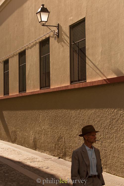 Senior man in hat walking down street, Cadiz, Andalusia, Spain