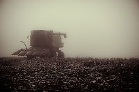 A corn harvester sits in the autumn morning's fog following the harvesting of the year's crop.