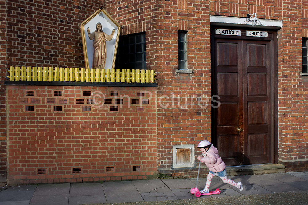 A small girl kicks her leg on a toy scooter, past an effigy of Jesus Christ encased in a shrine box outside a Catholic church in Camberwell, south London. The lady passes beneath the dominating figure that stands above the pavement. Encased in a glass-sided box and behind what resembles yellow garden fencing, the Christian idol stands with outstretched arms, a traditional figure for Catholics to practice idolatry. The church walls are constructed from red brick, in a style much-seen in industrial buildings.