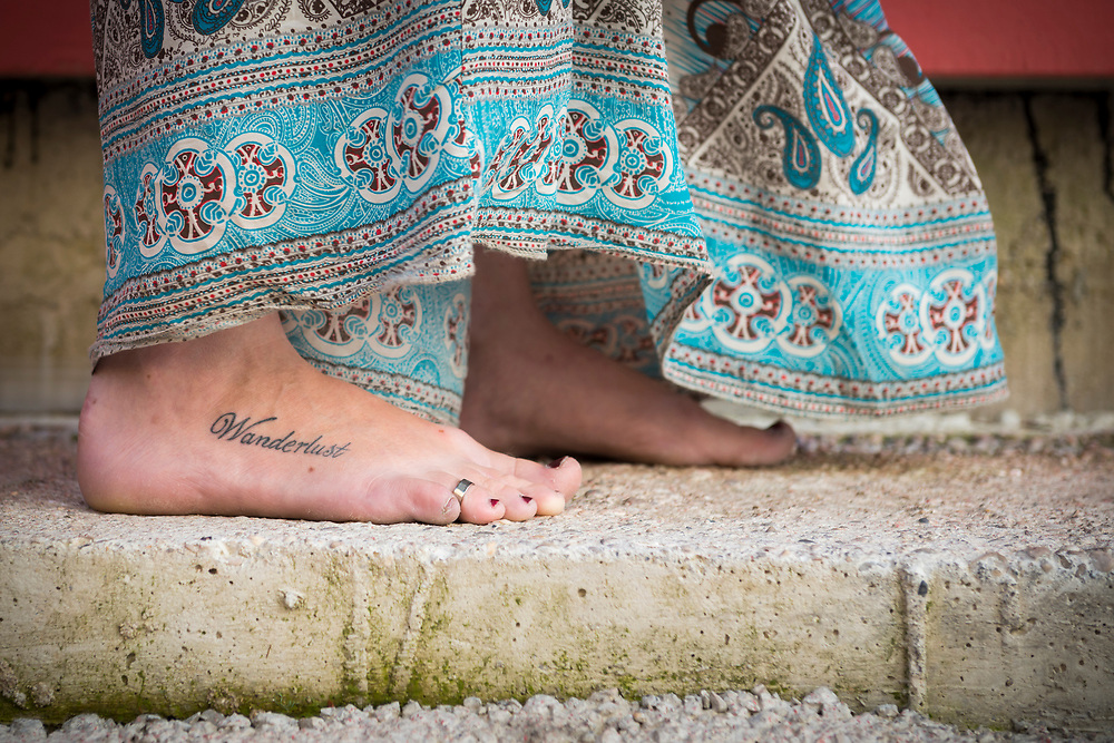 """A young woman standing barefoot with the word """"Wanderlust"""" tattooed on her foot"""