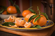 Tangerine Dream by Rodney Bedsole, a food photographer based in Nashville. Tangerines with twigs and leaves on a blue and yellow plate.