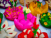 """03 NOVEMBER 2017 - BANGKOK, THAILAND: Krathongs for sale during Loi Krathong at Wat Prayurawongsawat on the Thonburi side of the Chao Phraya River. Loi Krathong is translated as """"to float (Loi) a basket (Krathong)"""", and comes from the tradition of making krathong or buoyant, decorated baskets, which are then floated on a river to make merit. On the night of the full moon of the 12th lunar month (usually November), Thais launch their krathong on a river, canal or a pond, making a wish as they do so. Loi Krathong is also celebrated in other Theravada Buddhist countries like Myanmar, where it is called the Tazaungdaing Festival, and Cambodia, where it is called Bon Om Tuk.     PHOTO BY JACK KURTZ"""