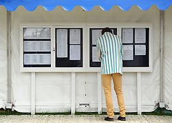 © Licensed to London News Pictures. 27/06/2012. Henley-on-Thames, UK. A man looks at the results board. Spectators watch rowing crews compete at the Henley Royal Regatta on June 26, 2012 in Henley-on-Thames, England. The 172-year-old rowing regatta is held 27th June- 1st July 2012. Photo credit : Stephen Simpson/LNP