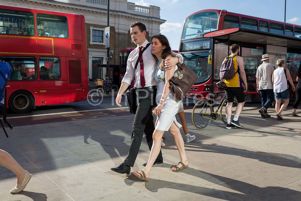 A couple walk arm in arm while commuters walk southwards over London Bridge, from the City of London - the capitals financial district founded by the Romans in the 1st century - to Southwark on the south bank, on 2nd August 2018, in London, England.