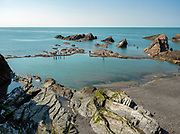 Ilfracombe Sea Pool with people walking the perimeter containment walls on a peaceful English May Day.  Licensing and Open Edition Prints.