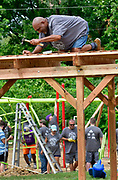 Anthony Randle, Sr. climbed atop this shade structure to nail cross pieces in place. He is the father of first and third grade students at Highland Elementary School. Volunteers from the Pacific Life Foundation, Edward Jones, the Riverview Gardens School District, the Boys & Girls Clubs of Greater St. Louis and the community joined KaBOOM! and transformed an empty site into a kid-designed, state-of-the-art playground at Highland Elementary School on Saturday August 18, 2018. The playground - designed from students' drawings - will give more than 400 kids a safe place to play. KaBOOM! is a national non-profit dedicated to bringing balanced and active play into the daily lives of all kids.  Photo by Tim Vizer