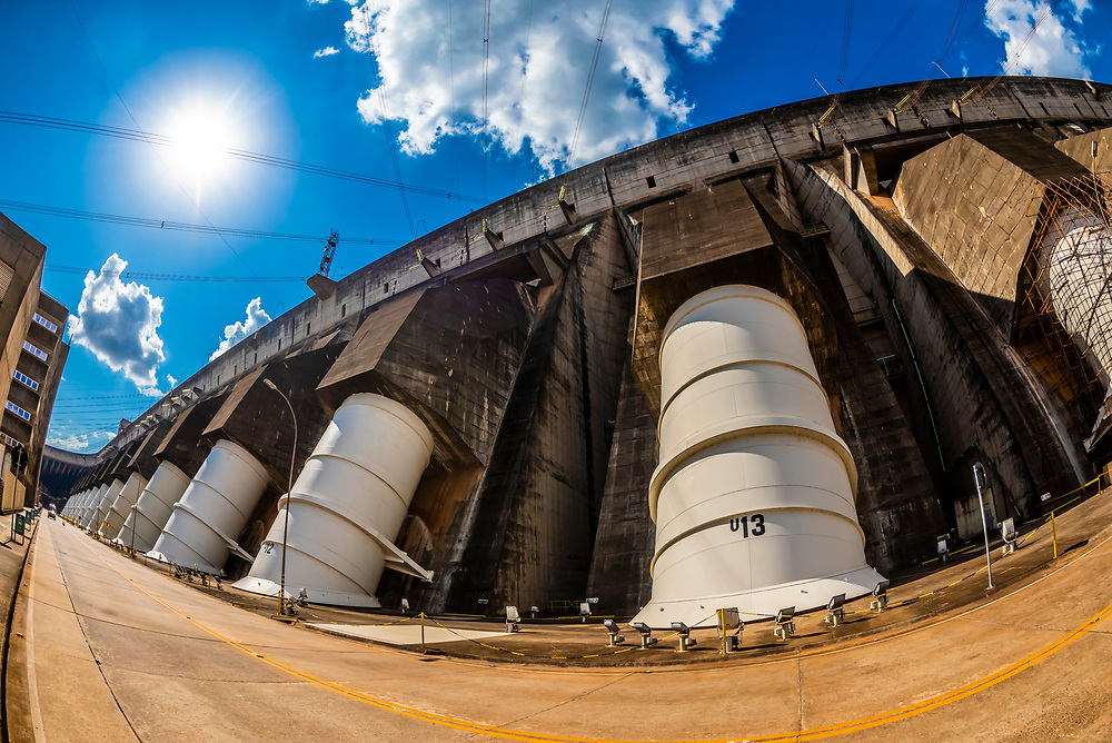 Penstocks (huge pipes that carry water from the Itaipu Dam above into the Itaipu Hydroelectric power plant to the turbine, where the power is created. Brazil/Paraguay border.                                   In terms of power output, Itaipú Dam is one of the world's largest hydroelectric projects. Its 20 massive turbine generators, located in the powerhouse at the base of the dam, are capable of generating 14,000 megawatts of electricity.