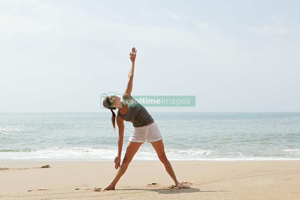 Jul. 25, 2012 - Woman practicing yoga on a beach (Credit Image: © Image Source/ZUMAPRESS.com)