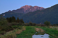 Mount Blandshard (The Golden Ears) after sunset from the dike along the Pitt River in Pitt Meadows, British Columbia, Canada
