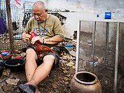 20 MARCH 2017 - BANGKOK, THAILAND: A man tends to his fighting cocks in a temporary tent in Pom Mahakan. The old fort used to be a center of the Thai cock fighting sport. The final evictions of the remaining families in Pom Mahakan, a slum community in a 19th century fort in Bangkok, have started. City officials are moving the residents out of the fort. NGOs and historic preservation organizations protested the city's action but city officials did not relent and started evicting the remaining families in early March.               PHOTO BY JACK KURTZ