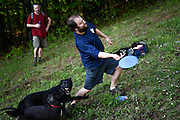Peter Bolduc, of West Lebanon, side arms a disc up a steep fairway on the Storrs Pond disc golf course despite the playing dogs of fellow disc golfers James Beaulieu, left, and Spencer Weatherholt, not pictured, in Hanover, N.H. Thursday, May 21, 2015. Beaulieu designed the course to be challenging, but scenic with steeply contoured terrain and fairways spotted with obstacles. (Valley News - James M. Patterson)<br /> Copyright © Valley News. May not be reprinted or used online without permission. Send requests to permission@vnews.com.