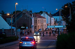 © Licensed to London News Pictures. 09/08/2015. Calais, France. A large group of migrants cross a road in the town of Freshen near Calais in Northern France as they head to  the train tracks to the Eurotunnel terminal terminal. Hundreds of migrants attempt to illegally access the Eurotunnel complex each night in order to board a train and reach the UK. Photo credit: Ben Cawthra/LNP
