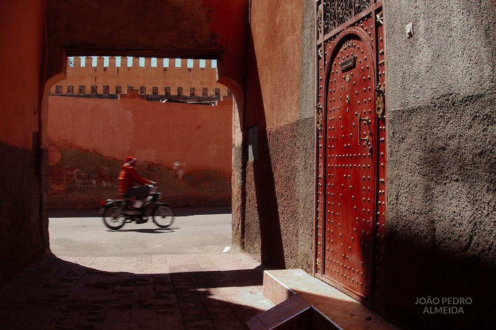 A red door at a narrow street of the medina of Marrakech