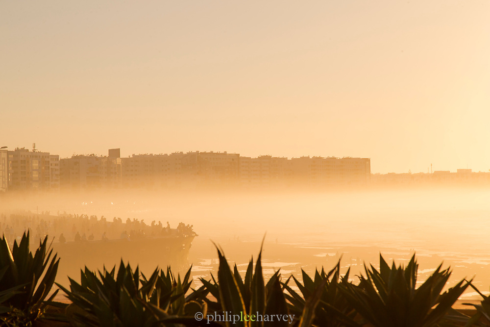 Silhouettes of tourists on beach at foggy sunset, Casablanca, Morocco