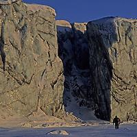 SPITSBERGEN, Svalbard, Norway. Polar expeditioneer under glacier cliffs at Inglefield Bay on island's east coast.