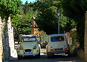 Two vintage French cars, the Citroen deux chevaux parked side by side on a narrow lane,18th October 2008, Lagrasse, France.