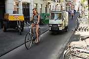 Nederland, Utrecht, 30-06-2015<br /> Een meisje fietst al bellend over het fietspad bij de Biltstraat in Utrecht met achter haar een brommobiel van 'De keuken van Thijs.'<br /> <br /> A girl is cyling while phoning at a bike line at the Biltstraat in Utrecht. Behind her is a moped truck.<br /> Foto: Bas de Meijer / Hollandse Hoogte