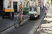 Nederland, Utrecht, 30-06-2015<br /> Een meisje fietst al bellend over het fietspad bij de Biltstraat in Utrecht met achter haar een brommobiel van 'De keuken van Thijs.'<br /> <br /> A girl is cyling while phoning at a bike line at the Biltstraat in Utrecht. Behind her is a moped truck.<br /> Foto: Bas de Meijer / Hollandse Hoogte