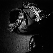 A 16-year-old ex-child soldier sits under his belonging in a room at the protection center by CERAO in Beni, a northern tip of Nord Kivu. Child soldiers from different factions also are responsible for looting and rape at will, growing up to be rebels.