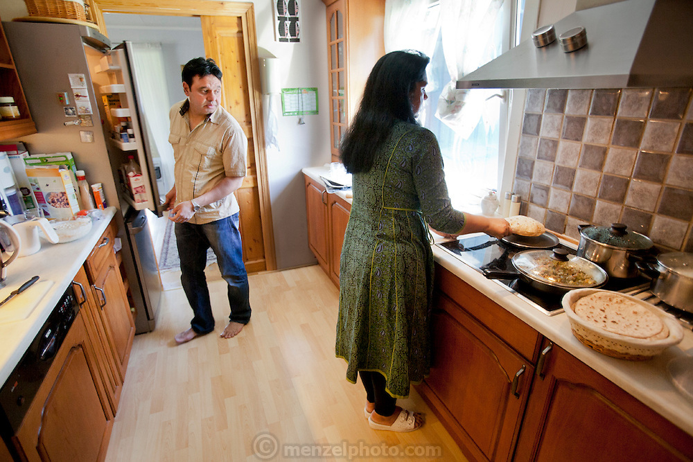 The Qureshi family of Lorenskog, Norway, an Oslo suburb. Pritpal Qureshi, 49, preparing chapati, unleavened flat bread, in her kitchen.  Her husband Nasrullah, 51, is at the refrigerator. Model-Released.