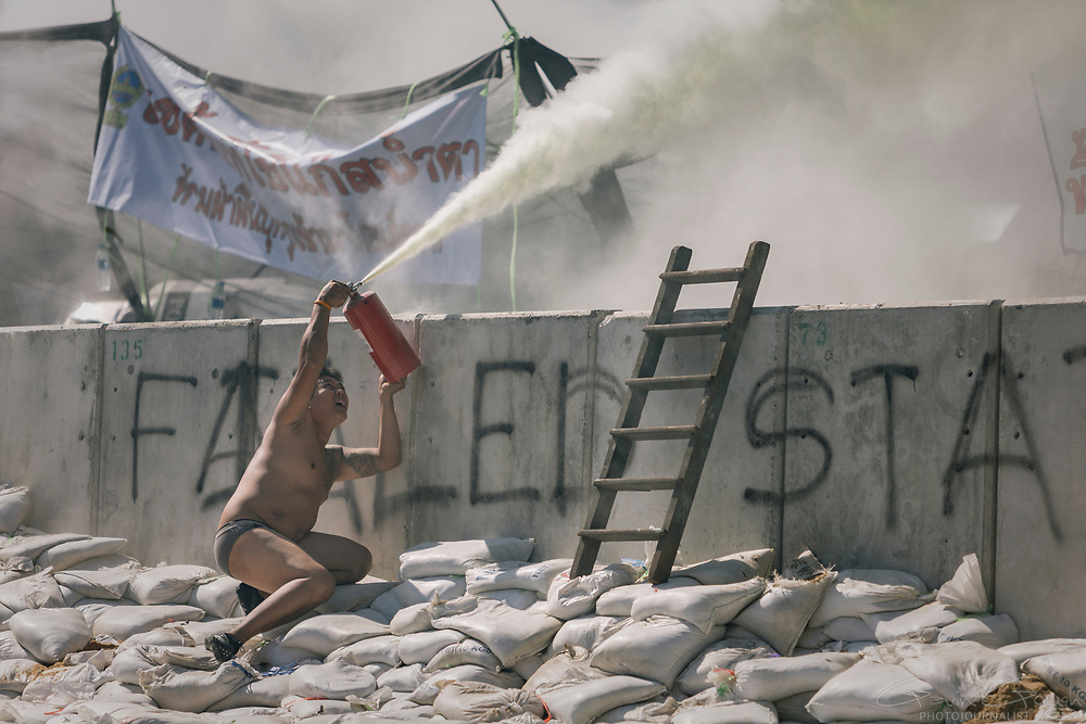 A protester dressed only in underpants sprays a fire extinguisher over barricades towards police lines during a stand-off between anti-Government protesters and police at Government House in Bangkok.