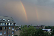 Plane flying across a double rainbow in the sky above a housing development in Wapping, London, UK.