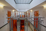 A wing of orange doors inside HMP Bronzefield, a private prison run by Sodexo Justice Services on the outskirts of Ashford in Middlesex, United Kingdom. HMP Bronzefield is an adult and young offender female prison, the only purpose built private prison solely for women in the UK and is the largest female prison in Europe. (photo by Andy Aitchison)