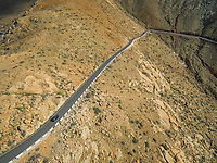 Aerial view of of a car driving on the famous winding mountain road that links the small towns of Casillas del Ángel and Pájara in Fuerteventura, Canary Islands.